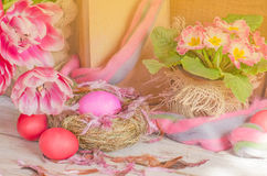 Pink easter eggs in nest and tulips. Background with easter eggs. Pink Easter eggs and nest on wodden background. Easter photo concept Royalty Free Stock Photo