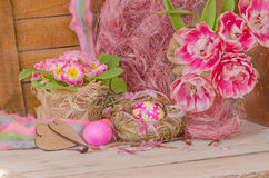 Pink easter eggs in nest and tulips. Background with easter eggs. Pink Easter eggs and nest on wodden background. Easter photo concept Stock Photo