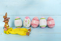 Pink easter eggs and rabbit  on a blue  wooden background Royalty Free Stock Photos
