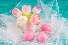 Pink easter eggs and tulips in a vase on white fabric and blue wooden background. Royalty Free Stock Photos
