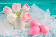 Pink easter eggs and tulips in a vase on white fabric and blue wooden background. Royalty Free Stock Images