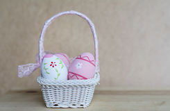Pink  easter eggs in white straw basket Royalty Free Stock Photography