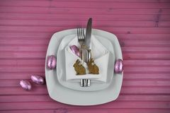 Pink Easter table place setting with white crockery and shiny eggs with wood bunny rabbit shape decorations stock images