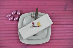 Pink Easter time table place setting in white with chocolate wrapped eggs and decorations Royalty Free Stock Photography