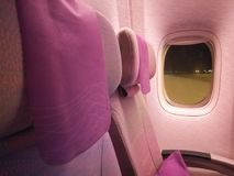 Pink economy seats of airplane at night. Pink economy seats of an airplane preparing to take off at night Royalty Free Stock Image