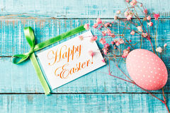 Pink egg with flowers and Happy Easter greeting card on blue woo Stock Photo