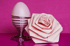egg and paper flower. A pink egg and a pink paper rose on a pink background Stock Image