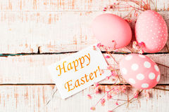 Pink eggs with flowers and Happy Easter greeting card on white w Stock Photos