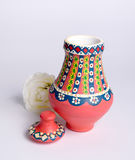 Pink Egyptian handmade decorated colorful pottery vase Kolla. Pink Egyptian decorated colorful pottery vase arabic: Kolla made of clay and white flower on white Stock Images
