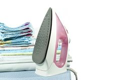 Ironing of clothes. Pink electric iron and a stack of ironed clothes on an ironing board on a white background Stock Image