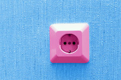 Pink electric socket on blue wall Stock Photos