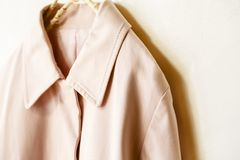Pink elegant trench coat isolated over white. A pink elegant trench coat isolated over white.Close up Royalty Free Stock Image