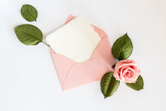 Pink envelop with white card and rose. Flat lay. Stock Image