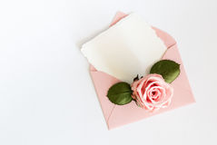 Pink envelop with white card and rose. Flat lay. Royalty Free Stock Image