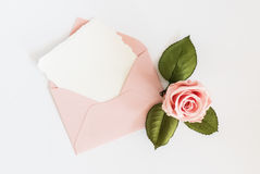Pink envelop with white card and rose. Flat lay. Stock Photography