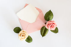 Pink envelop with white card and roses. Flat lay. Stock Images