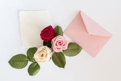 Pink envelop with white card and roses. Flat lay. Stock Photos