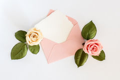 Pink envelop with white card and roses. Flat lay. Royalty Free Stock Images