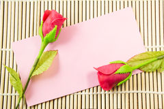 Pink envelope with artificial red rose. On bamboo background stock photo