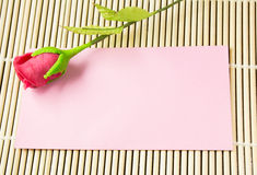 Pink envelope with artificial red rose. On bamboo background stock photography