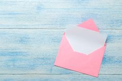 Pink envelope with blank form for text on a blue wooden table. top view stock photos