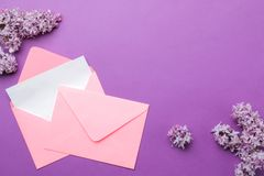 Pink envelope with a blank for the inscription and a sprig of lilac on a bright trendy lilac background. top view. Pink envelope with a blank for the inscription royalty free stock photos