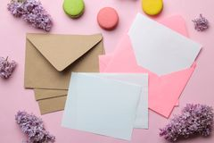 Pink envelope with a blank for text and a branch of lilac and macarons on a bright trendy pink background. top view stock photos