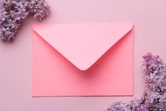 Pink envelope and branch of lilac on a bright trendy pink background. top view stock image