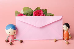 Pink envelope with couple doll Royalty Free Stock Image
