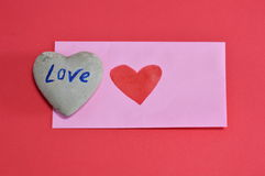 Pink envelope and heart rock on red color foam board Royalty Free Stock Photography