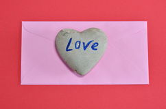 Pink envelope and heart rock on red color foam board Stock Photography