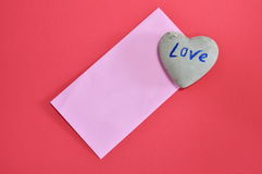 Pink envelope and heart stone on red color foam board Stock Photos