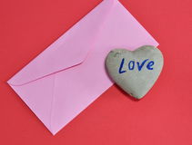 Pink envelope and heart stone on red color foam board Royalty Free Stock Photos