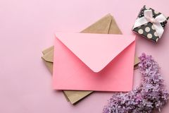 Pink envelope, lilac branch and gift box on a bright trendy pink background. top view. Pink envelope, lilac branch and gift box on a bright trendy pink royalty free stock photos