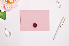 Pink envelope with a rectangular flip, Mockup. Wax seal, pen, flower and wedding decoration. Royalty Free Stock Photos