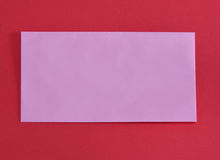 Pink envelope on red color foam board Royalty Free Stock Images
