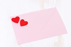 Pink envelope with red hearts on a white wooden background Stock Photo