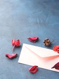 Pink envelope for romantic love letter. Pink envelope with dried flowers petals on dark blue background. Valentine`s day. Sending Love letter royalty free stock photography