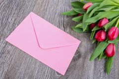 Pink envelope with tulips on a table. Pink envelope with tulips on a wooden table stock photo