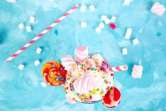 Pink Extreme milkshake with berry rasberry. Pink Extreme milkshake with berry, rasberry, strawberry, candy marshmallow, lollipops on blue background.. Crazy Royalty Free Stock Image