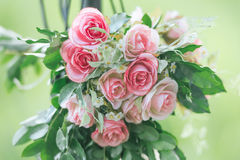 Pink fabric rose flowers bouque vintage on green background with Stock Image