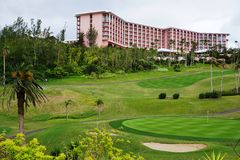 The pink Fairmont Hotel in Southampton, Bermuda. SOUTHAMPTON, BERMUDA -The pink Fairmont Southampton hotel on the South Shore of Bermuda overlooks green hills royalty free stock photography