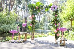 Pink fake flamingo wedding decoration with anthurium flowers and. Monstera leafs, colorful balloons on arch. Meadow in green garden, summer daylight Royalty Free Stock Photos
