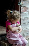 Pink farm girl and kitten. An adorable little farm girl in pink overalls holds a new baby kitten found in the  barn Royalty Free Stock Photo
