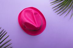 Pink fashion summer hat isolated on the violet or puprle backgound, beach summer concept and holiday concept flat lay royalty free stock photo