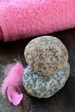 Pink feather on the stones and pink towel Royalty Free Stock Photography