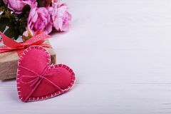 Pink felt heart, flowers and handmade gift on a white wooden table, Concept, banner, save space stock photography