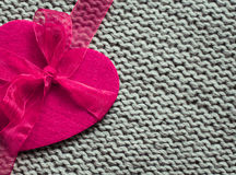 Pink felt heart with knitted woolen texture as a background Stock Photo