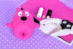 Pink felt Teddy bear, handmade felted toy. Scissors, needle, thread, pins, paper templates - sewing kit Stock Photos