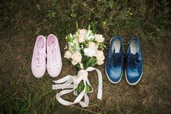Pink female trainers shoes and blue male trainers shoes. Closeup top view of pink female trainers shoes and blue male trainers shoes standing on ground outdoors stock photos